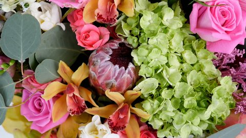 close-up, view from above, Flowers, bouquet, rotation, floral composition consists of Rose aqua, Ornithogalum, Brunia green, eucalyptus, Cymbidium orchid, Protea, Barbatus,