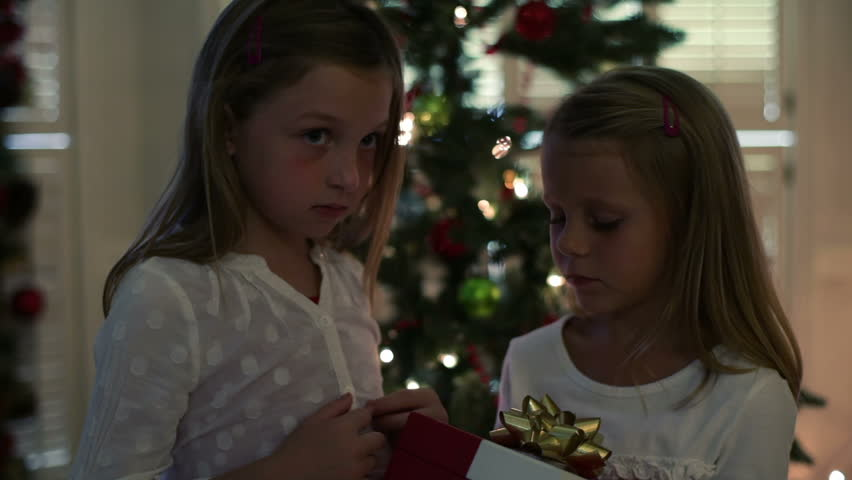 Two cute little blond girls standing in front of a Christmas tree open a box that reveals a bright light from inside.