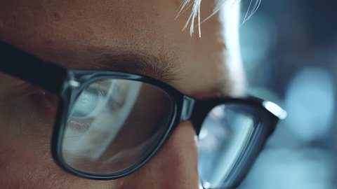 Closeup of male eyes looking at screen of laptop or computer, businessman working late at office