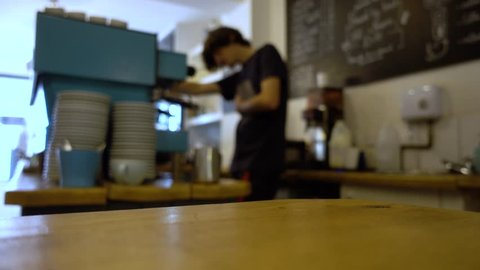 Barista places an espresso on the table