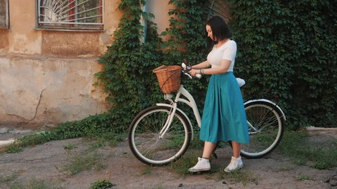 Beautiful young woman with short brunette hair wearing long retro style skirt walking the old street with lush foliage near vintage white bicycle with basket. Slow Motion.