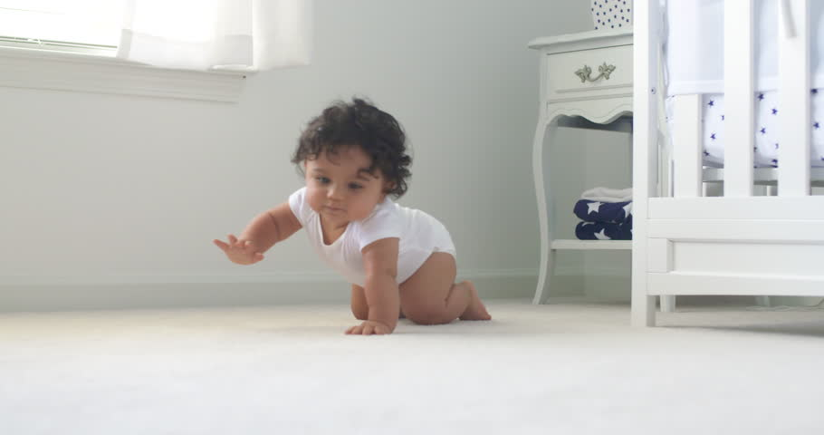 Baby Crawls Toward Rack Focus Low Angle Slow Motion. Baby crawls toward the camera in slow motion smiling and laughing in a white room