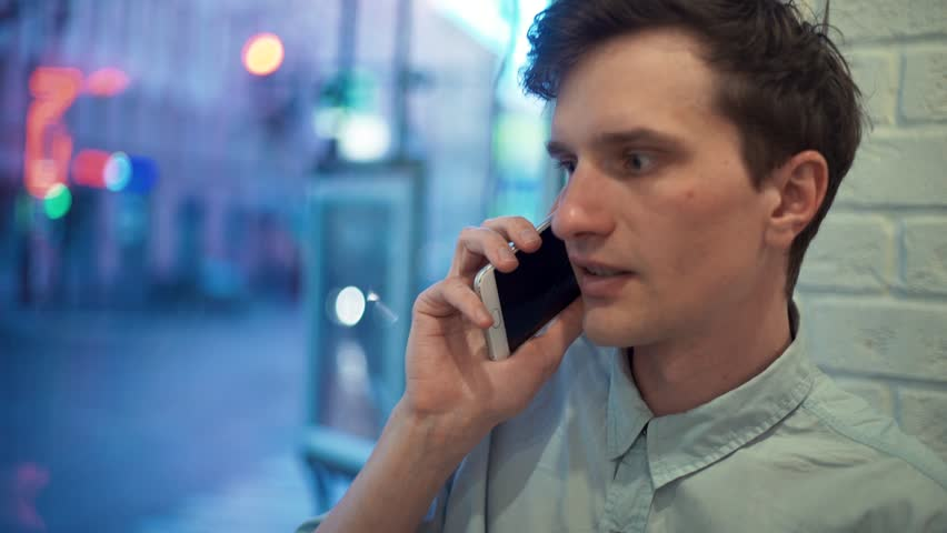 Young man in blue shirt talking on phone in cafe in evening. Street traffic outside the window | Shutterstock HD Video #28330507