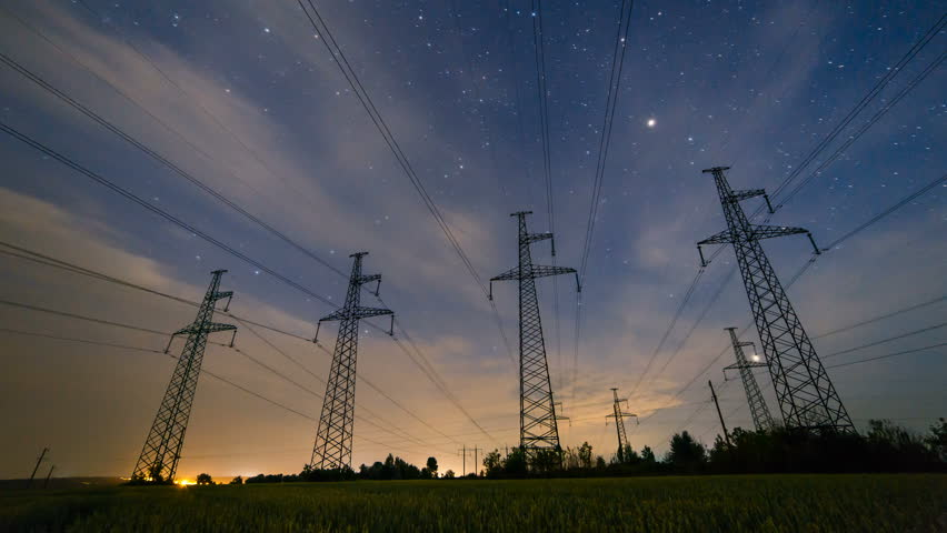 Silhouette of four electricity pylons on the wheat field from beautiful sunset till nightly starry sky. Day to night time lapse of high-voltage power lines ends with flashes of lightning.