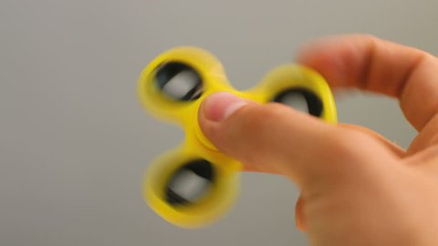 Yeloow spinner fidget device in hand.Man playing with new spinning toy.Popular gadget with bearings in the middle