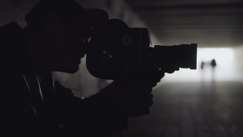 Cinema shooting. The cameraman shoots a movie on vintage camera. Silhouette