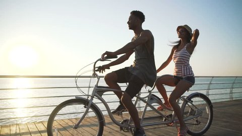 Portrait of a mixed race couple riding on tandem bicycle outdoors near the sea, slow motion