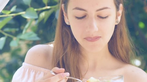 Young woman eating yogurt. Healthy summer diet.
