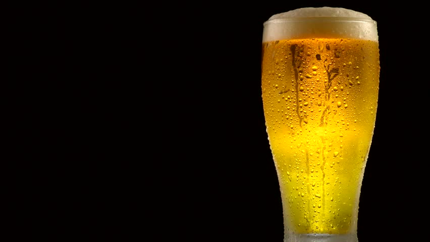 Cold Light Beer in a glass with water drops over matte black background, border design. Craft Beer close up. Copy space for your text. Rotation 360 degrees. 4K UHD video 3840x2160