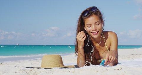 Beach vacation. Woman wearing earphones listening to music or audiobook starting book or song on smart phone app. Girl in bikini sunbathing relaxing on beach putting on in-ear headphones.