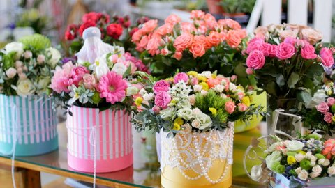 Flower shop, on the show-window, there are a lot of bouquets of flowers from pion-shaped roses, floral stylish compositions in colorful boxes with different flowers