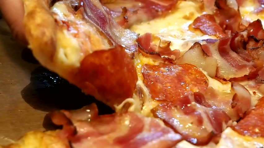 Takes eating a slice of pizza with cheese, tomatoes and ham. Delicious food for gluttony and enjoyment. Culinary masterpiece close-up.