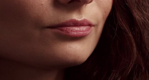 closeup of woman's mouth biting a bar of chocolate truffle covered by chocolate powder