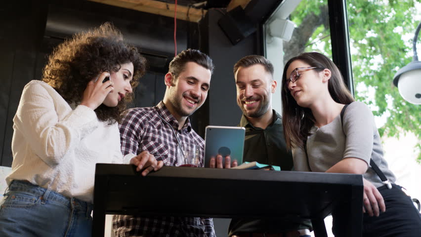 Happy Trendy Group Of Friends Standing Together Around A Bar Table Passing iPad Looking At Video Laughing Smiling Talking On Phone At Restaurant Slow Motion Shot On Red Epic 8K