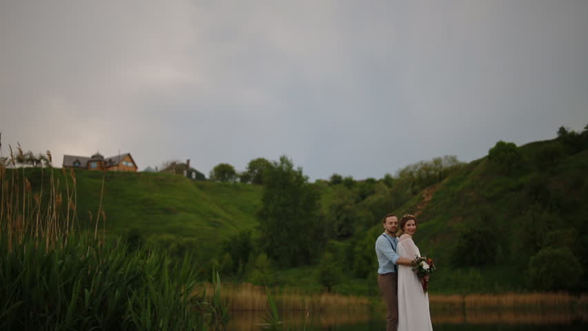 Girl approach on field with haystacks stock footage video 12093386 bride and groom posing on the wooden pier near the pond young people embrace each ccuart Gallery