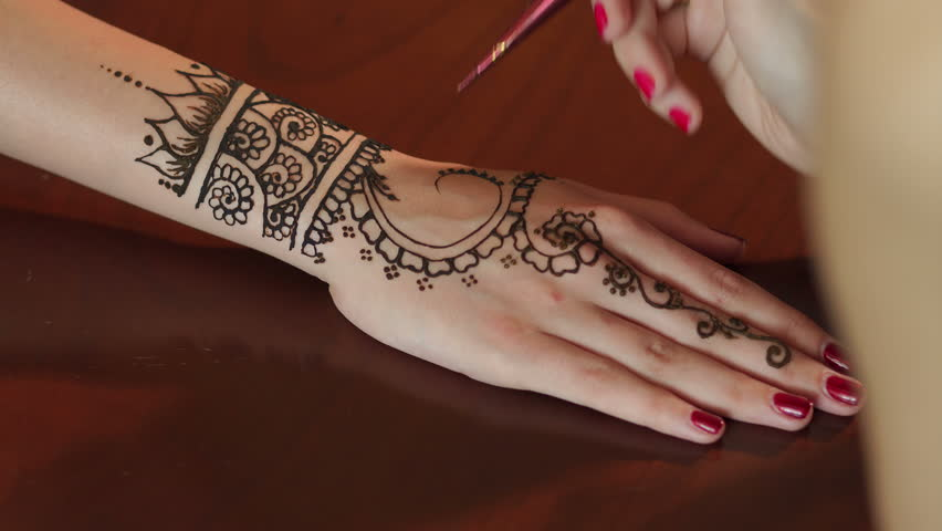Mehndi Tattoo On Hand For Girls : Process of applying mehndi on female's hand close up. creative girl
