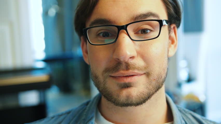 Portrait of young handsome man in blue shirt with glasses working on the laptop in the living room at home while sitting on the sofa. Close up.   Shutterstock HD Video #28459486