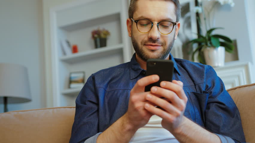 Young caucasian man with glasses and beard relaxing on couch using smart phone in modern industrial house. Indoor.