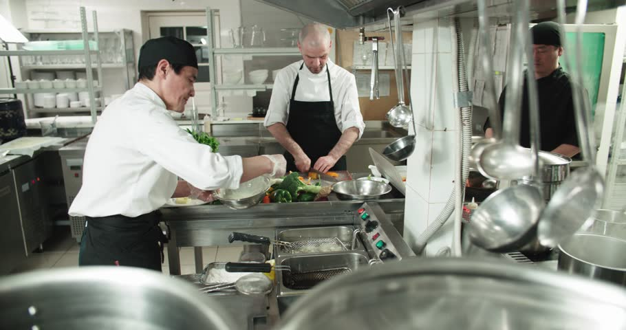 the workflow in the kitchen of the restaurant,a team of Asian chefs prepare dishes