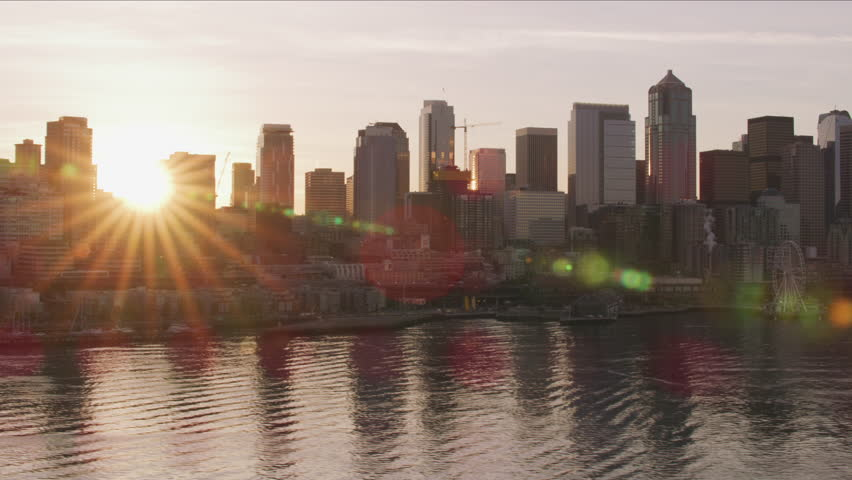 Seattle, Washington circa-2017, Sun peeks out from behind downtown Seattle buildings at sunrise. Shot with Cineflex and RED Epic-W Helium.
