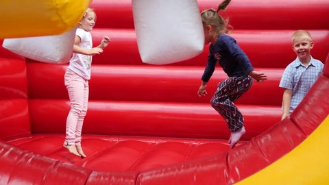 WROCLAW, POLAND - JUL 02, 2017: Kids Amuse Have Fun Jumping On The Inflatable Trampoline On Playground For Children