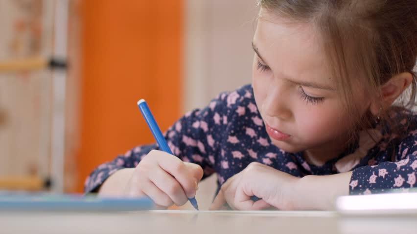 A little girl at her desk draws a blue felt-tip pen | Shutterstock HD Video #28506826