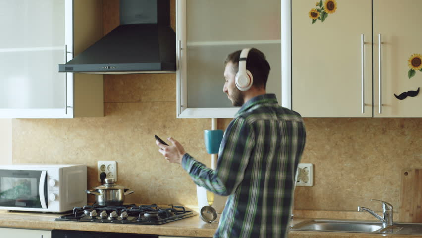 Handsome Young Funny Man In Headphones Dancing And Singing Kitchen At Home The Morning