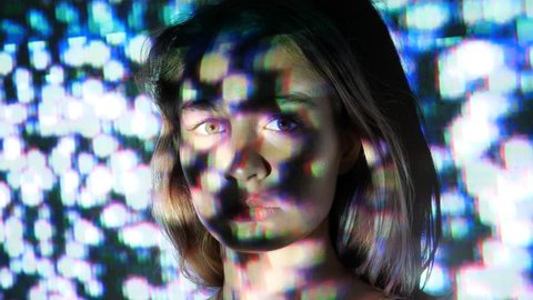 TV static plays on young womans face. Projected film on female model.