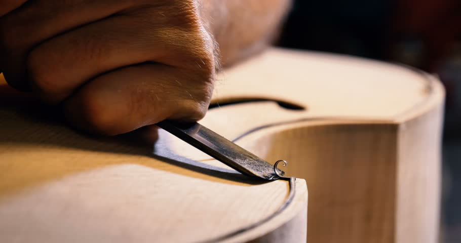 The professional violin master makes a violin with his own hands, uses a pure tree spruce, pine, makes patterns from a chisel, plane. Concept spiritual instrument, made hands, art, music, melody sound