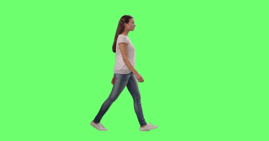 Casual Young Brunette Girl is Walking on a Mock-up Green Screen in the Background. Shot on RED Cinema Camera in 4K (UHD).