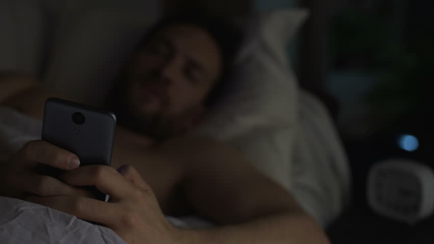 Young adult man can't sleep, yawning and browsing the net on cellphone, insomnia #28538296