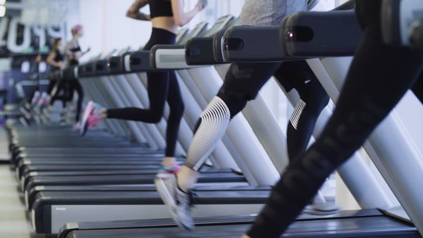 Legs of unrecognizable people running on the treadmill in the fitness studio. Runners in the gym | Shutterstock HD Video #28561876