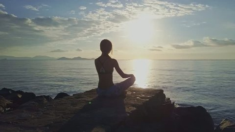 drone moves around girl sitting in pose ArdhaPadmasana against unforgettable sun reflection on ocean surface