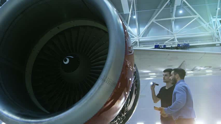 In a Hangar Aircraft Maintenance Engineer Shows Technical Data on Tablet Computer to Airplane Technician, They Diagnose Jet Engine Through Open Hatch. They Stand Near Clean Brand New Plane. 4K UHD.