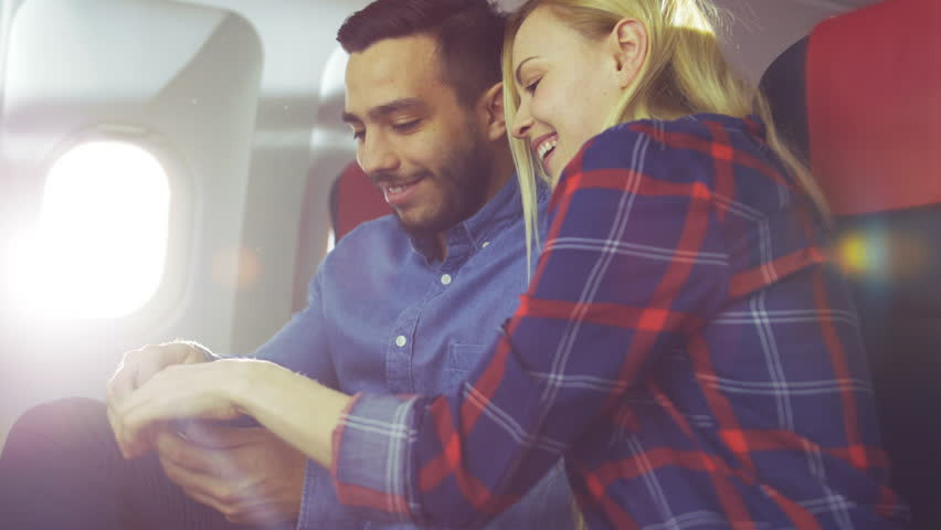 On a Board of Commercial Airplane Beautiful Young Blonde with Handsome Hispanic Male Watch Videos on Smartphone and Smile. Sun Shines Through Aeroplane Window. Shot on RED EPIC-W 8K Helium Camera. | Shutterstock HD Video #28618336