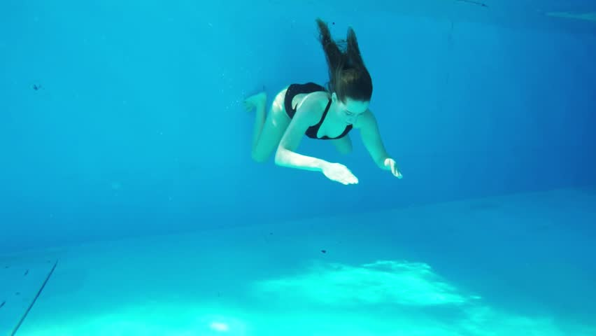SLOW MOTION: Underwater shot of a girl swimming in a swimming pool.