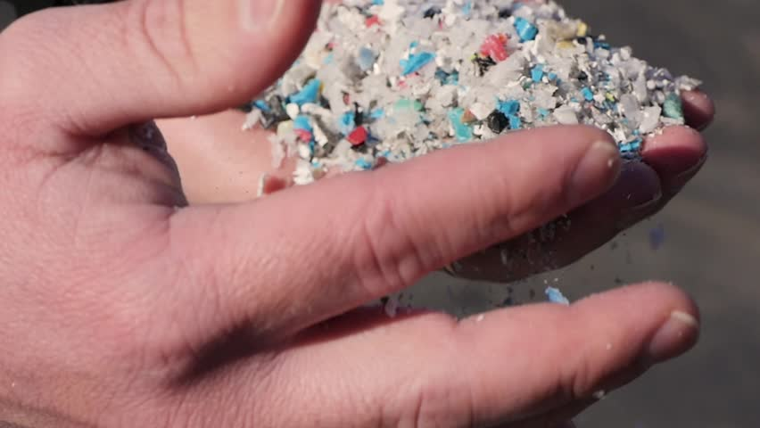This is a close up shot of a man's hands as he shows the camera a handful of recycled plastic pieces. He moves them from one hand to the other. Shot in slow motion. | Shutterstock HD Video #28675846