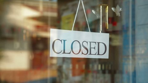 Business owner turns sign from closed to open in front of her store