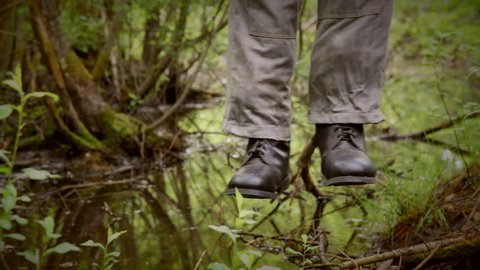 hanged man in boots over the rotten swamp