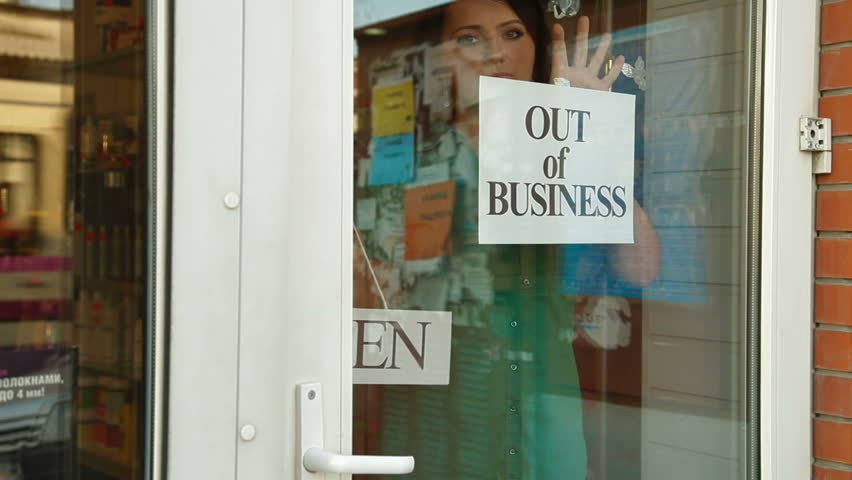 Business owner puts up Out Of Business sign on door of her store