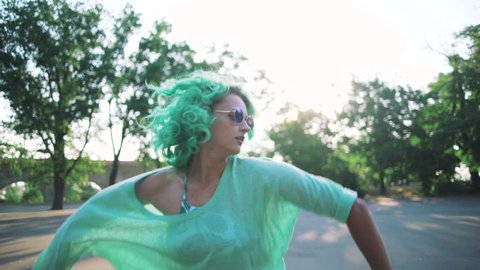 young stylish funky girl with green hair and sun glasses dancing outdoor, slow motion