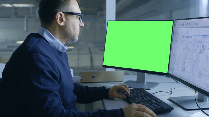 Chief Male Engineer Working on Technical Project on His Person Computer. Second Display Shows Mock-up Green Screen. Out of the Office Window Big Factory is Seen. Shot on RED EPIC-W 8K Helium  Camera. | Shutterstock HD Video #28698916
