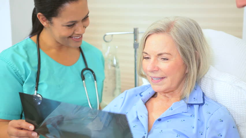 Elderly female hospital patient looking x-ray images with radiologist medical staff | Shutterstock HD Video #2870083