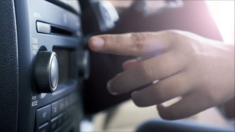 Close-up of female hand adjusting button audio on a vehicle's dashboard.