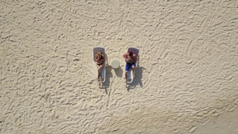 Aerial drone camera ascending and rotating high above the couple in love lying in the sun on beach bed deck chairs and drinking cocktails at empty tropical white sand beach on atoll island resort with