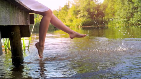 Woman sitting on the edge of a wooden jetty at lake, feet near the water surface, slow motion.