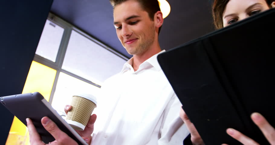 Group of friends using mobile phone and digital tablet while having cup of coffee in cafe | Shutterstock HD Video #28727536