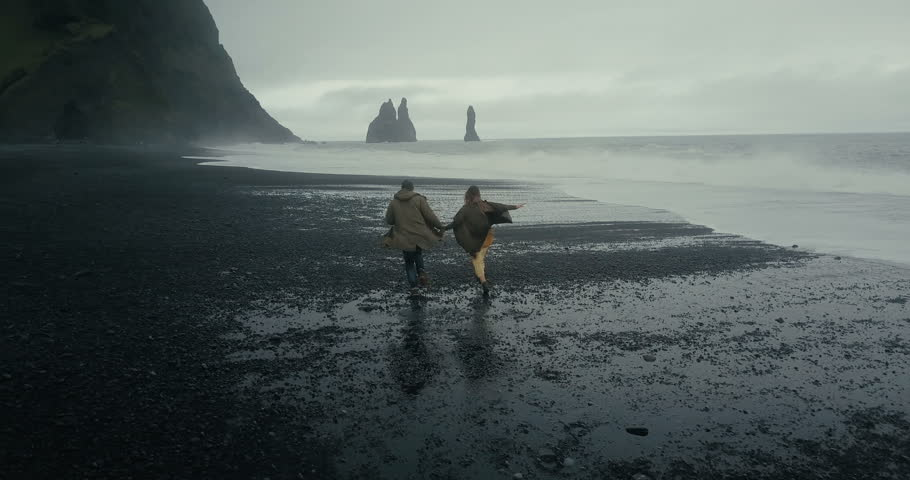 Back aerial view of young hipster couple running on the black volcanic beach near the troll toes in Iceland. #28728346