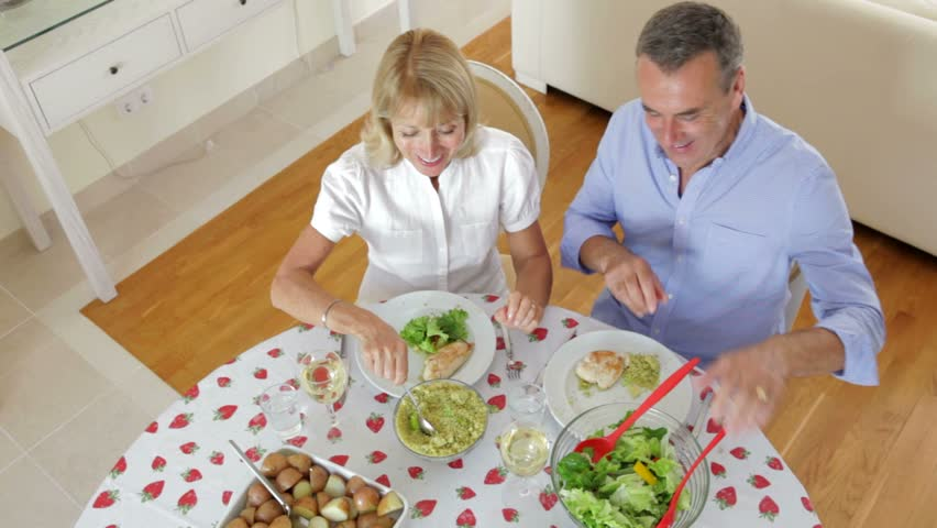 Senior couple seated around dining table serving one another from above.