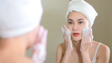 Woman cleaning washing her face with foam in bathroom.